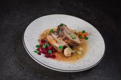 Grisköttstöd med beta, morötter, stekte champinjoner och sås på en vit platta Restaurangportion Gammal svart lantlig bakgrund öve royaltyfri bild