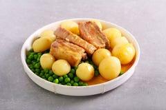 Grisköttstöd, potatis och ärtor arkivbilder