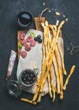 Grissini面包条、被治疗的猪肉香肠、橄榄和红葡萄酒 免版税库存照片
