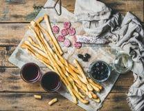 Grissini面包条、香肠、橄榄和红葡萄酒,木背景 免版税库存照片