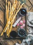 Grissini面包条,香肠,黑橄榄,在木盘子的酒 免版税库存图片