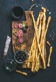 Grissini面包条,香肠,黑橄榄,在黑暗的背景的酒 免版税图库摄影