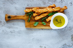 Grissini bread sticks. Fresh baked grissini bread sticks on wooden cutting board with olive oil and herbs rosemary and basil over grey concrete textured surface royalty free stock photo