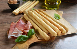 Grissini. Bread sticks with ham on old wooden background stock image