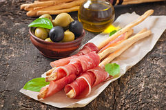 Grissini bread sticks with ham Stock Photography