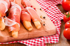 Grissini breadsticks with ham. Royalty Free Stock Image
