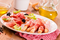 Grissini breadsticks with ham. Royalty Free Stock Photo