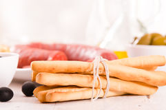 Grissini breadsticks with salami. Stock Image