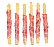 Grissini de batons de pain avec le prosciutto d'isolement sur le fond blanc Photo stock