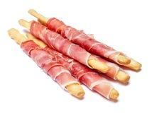 Grissini de batons de pain avec le prosciutto d'isolement sur le fond blanc Image stock