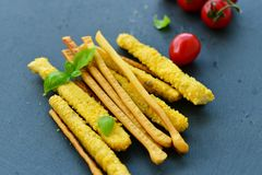 Grissini. Different types of grissini - tradition Italian breadsticks and mini san Marzano italian cherry tomatoes. Mediterranian lunch stock image