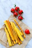 Grissini. Different types of grissini - tradition Italian breadsticks and mini san Marzano italian cherry tomatoes. Mediterranian lunch stock images