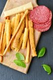 Grissini. Different types of grissini - tradition Italian breadsticks, fresh basil,yellow cheese and salami. Mediterranian lunch royalty free stock photography