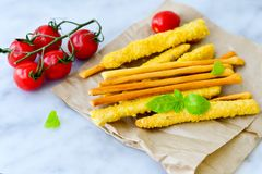 Grissini. Different types of grissini - tradition Italian breadsticks and mini san Marzano cherry tomatoes. Mediterranian lunch stock image