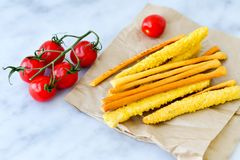 Grissini. Different types of grissini - tradition Italian breadsticks and mini san Marzano italian cherry tomatoes. Mediterranian lunch stock photography