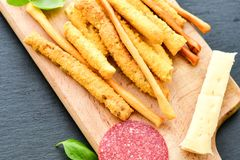 Grissini. Different types of grissini - tradition Italian breadsticks, yellow cheese and salami. Mediterranian lunch royalty free stock images