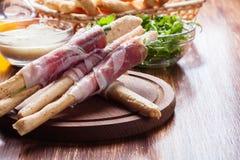 Grissini italiano con il prosciutto di Parma, la mozzarella e la rucola del prosciutto Fotografia Stock