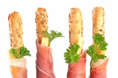 Grissini with prosciutto. Four vertically arranged grissini sticks with delicious prosciutto, cheese and parsley Royalty Free Stock Images