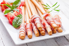 Grissini with prosciutto Stock Images