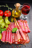 Grissini stick bread with ham on black board with appetizers Royalty Free Stock Photo