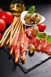Grissini stick bread with ham on black board Stock Images