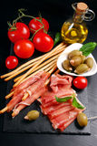 Grissini stick bread with ham on black board Royalty Free Stock Photo