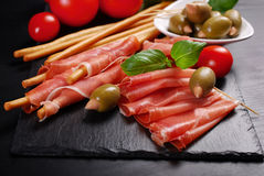 Grissini stick bread with ham on black board Stock Image