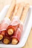 Grissini sticks with ham Stock Images