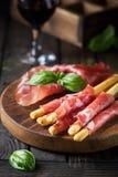 Grissini van broodstokken met prosciutto Stock Afbeeldingen