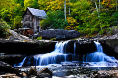 Grist Mill. Picture of an old grist mill sitting abouve a water fall during the early fall Stock Photo