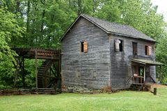 Gristmill surrounded by green foliage Royalty Free Stock Photography
