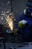 Gristrar bärande skyddsutrustning för arbetaren genom att använda en vinkelmolar på metall och göra Arkivfoto