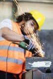 Gristrar kommande ut från molar med arbetaren i bakgrund på metallbransch Arkivbild
