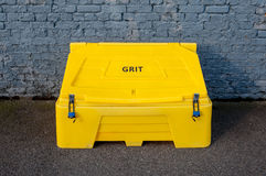 Grit bin against a brick wall Royalty Free Stock Image