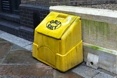 Grit salt. Yellow plastic box on street pavement Stock Image