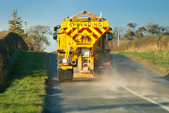 Grit Spreading. Winter service vehicle or gritter spreading rock salt on the road surface to prevent icing in winter which causes accidents when vhicles slip on Royalty Free Stock Images
