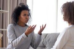 Gritaria afro-americano restrita irritada da mãe na filha adolescente foto de stock royalty free