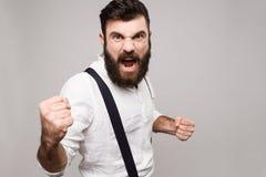 Gritaria considerável nova rude irritada do homem sobre o fundo branco Imagem de Stock
