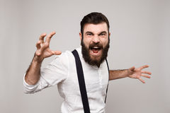 Gritaria considerável nova rude irritada do homem sobre o fundo branco Imagens de Stock