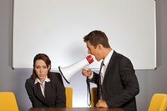 Gritaria da mulher de negócios no homem de negócios através do megafone Foto de Stock