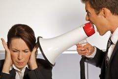 Gritaria da mulher de negócios no homem de negócios através do megafone Imagens de Stock