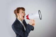 Gritaria de sorriso da mulher de negócios através do megafone fotografia de stock