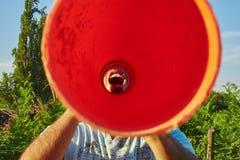 Gritaria do homem através de um tubo alaranjado imagem de stock royalty free