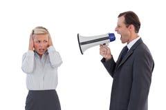 Gritaria do homem de negócios no colega com seu megafone Fotografia de Stock Royalty Free