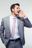 Gritaria do homem de negócios sobre o fundo cinzento Imagens de Stock