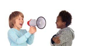 Gritaria engraçada da criança através de um megafone a seu amigo imagens de stock