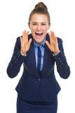 A gritaria feliz da mulher de negócio através do megafone deu forma às mãos Imagens de Stock