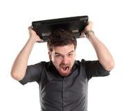 Gritaria furioso do homem de negócios em seu portátil Imagem de Stock