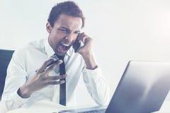Gritaria furioso do homem no smartphone foto de stock