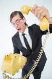Gritaria Geeky do homem de negócios e suspensão acima do telefone Imagens de Stock